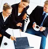 Business people dressed in formals discussing business matters with laptop