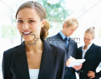 Confident happy business woman with her colleagues in the background