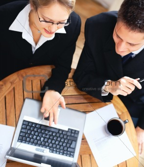Successful business people dressed in black formals working on laptop in the office