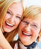 A young happy woman hugs an older happy elderly woman