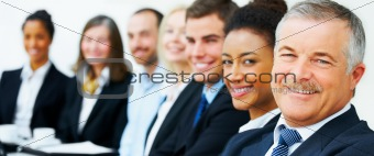 Happy business people seated in a row