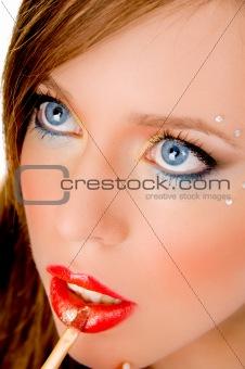 close up of beautiful woman applying lipstick