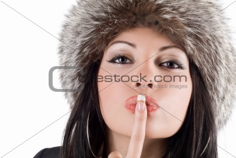 Portrait of the young woman with a finger at lips