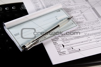 Preparing Taxes - Check and Forms on Keyboard
