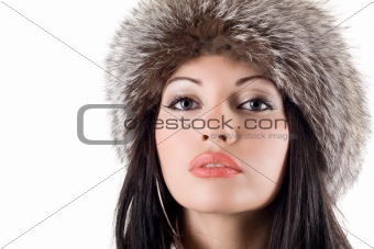 Portrait of the young woman in a fur cap