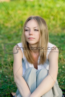 A beautiful young woman sitting in the grass