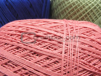 Three balls of wool  in blue, pink and green in a close-up view
