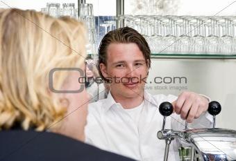 a proud bartender behind his bar
