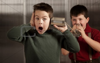 Little boy getting shocking message on tin can phone