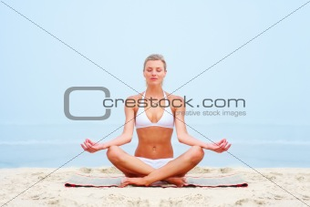 Sexy young woman in a lotus position at the beach