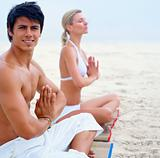 Young man and woman meditating at the beach