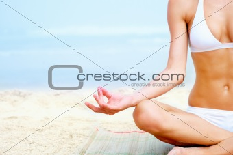 Cropped image of a woman meditating on beach