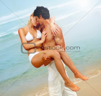 Handsome young man carrying his girlfriend on the beach