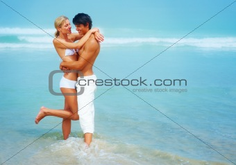 Romantic young couple standing together at beach