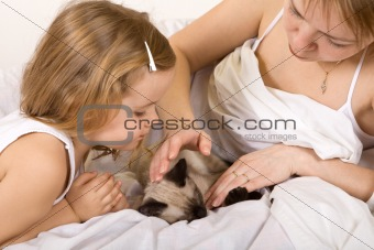Little girl and her mother stroking a kitten