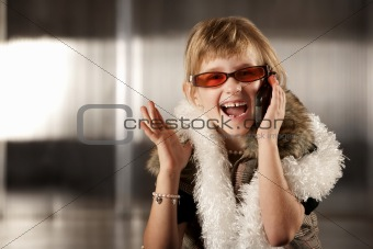 Cute young girl in red glasses talking on cell phone