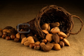 Assortment of nuts in basket on hesian background