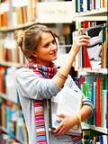 Female university student selecting book from shelf in a library