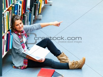 Woman sitting in the library pointing at something