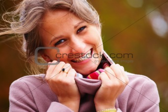 Charming woman smiling while holding her collar
