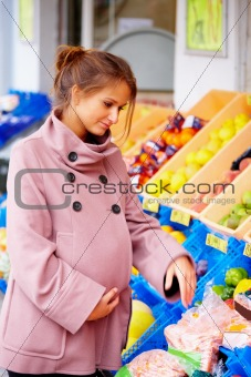 Pregnant woman shopping at fruit store