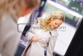 Pretty young girl trying out a jacket in a mall