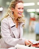 Young woman at supermarket checkout counter