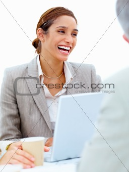 Laughing businesswoman using laptop
