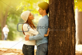 Romantic young couple standing by tree