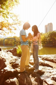 Romantic couple standing together on rocks
