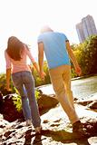 Rear view of a young couple walking  together by river