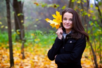 Beautiful young woman with a yellow leaf