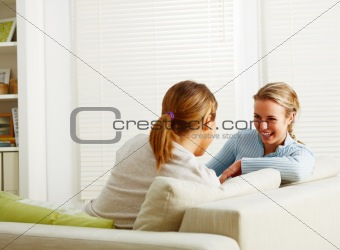 Young female friends sitting and chatting