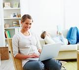 Woman using laptop while her friend lying on sofa