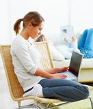 Young woman sitting on sofa and using laptop