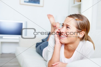 Young woman relaxing on couch and using cellphone