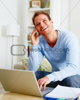 Happy young man using a computer laptop and cellphone