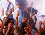 Men playing guitar and people raising hands at disco