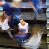 Motion blur of woman standing in busy school