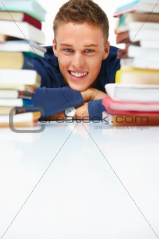 Portrait of smiling young boy with stack of books
