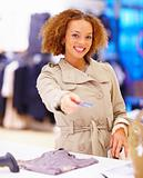 Smiling young woman giving credit card at cash counter