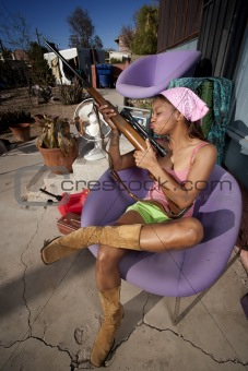 Black woman on back patio kissing rifle