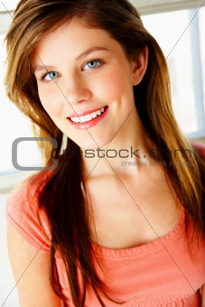 Portrait of attractive and smiling young woman against white background