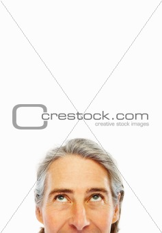 Cropped image an man 's face with his eyes looking upwards over white background