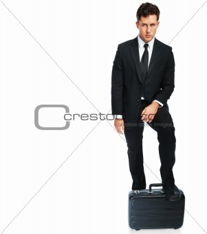 Business man standing with his leg on a suitcase