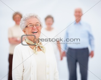 Happy senior woman with friends in background