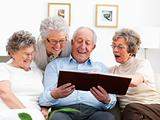Smiling old people viewing an album