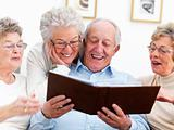 Group of smiling senior people viewing an album