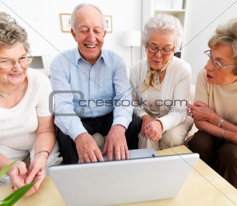 Group of happy senior people looking at laptop