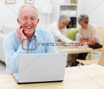 Smiling senior man with laptop, friends at home